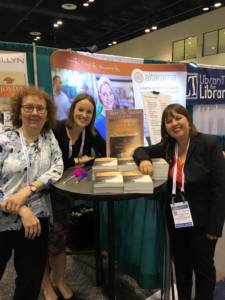 Paulette stopping for a picture of the amazing LLewellyn teamwork at ALA Orlando event, 2016.